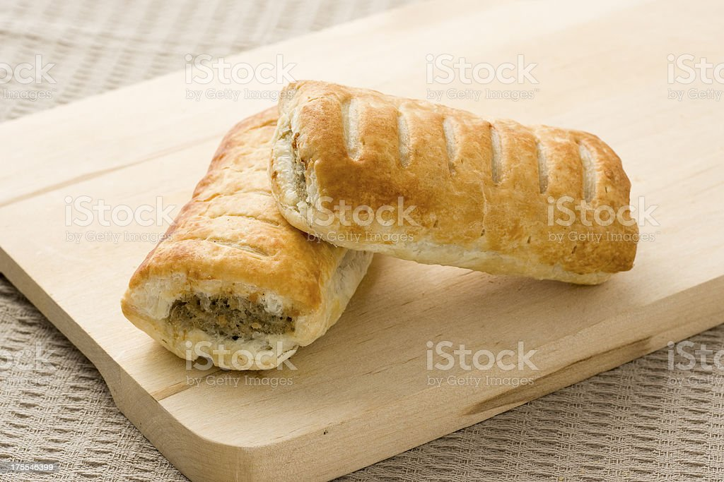Sausage roll pastry snack with meat on a wooden surface stock photo