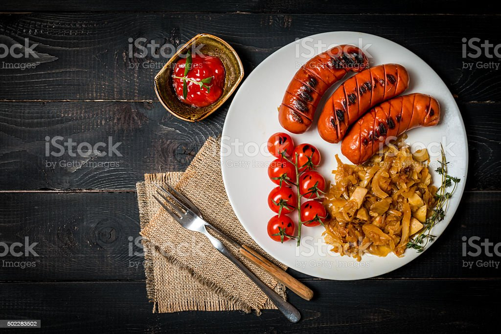 Sausages and fried cabbage stock photo