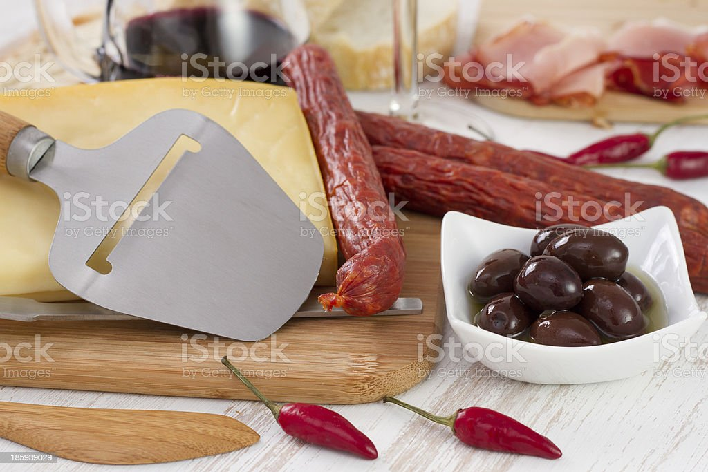 sausages, cheese, olives, bread and red wine on the table royalty-free stock photo