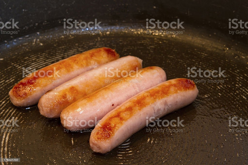 sausages frying with oil in the pan royalty-free stock photo