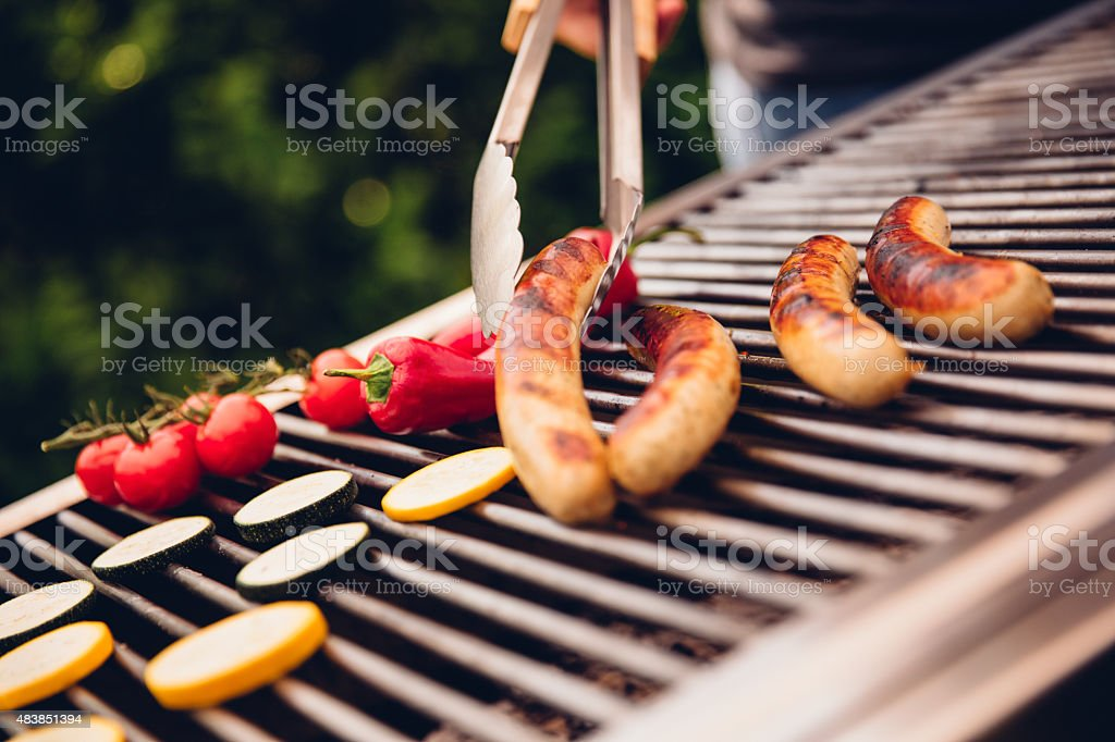 Sausages on an outdoor barbecue being turned stock photo