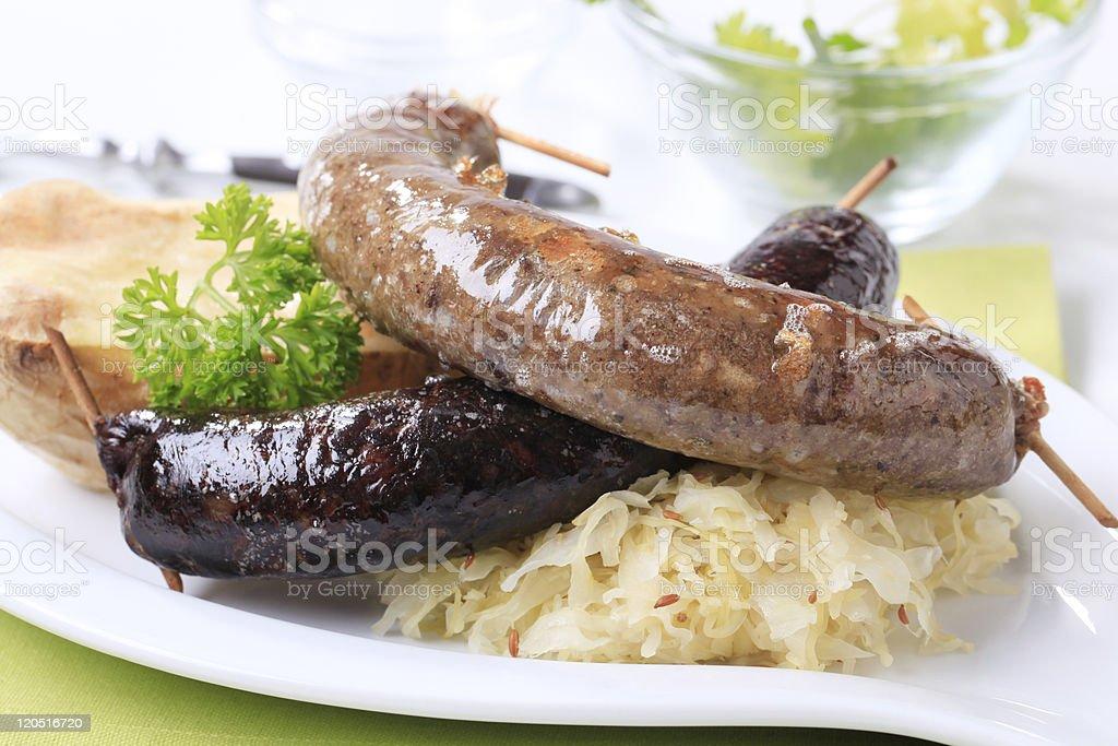 Sausages, sauerkraut and baked potato royalty-free stock photo