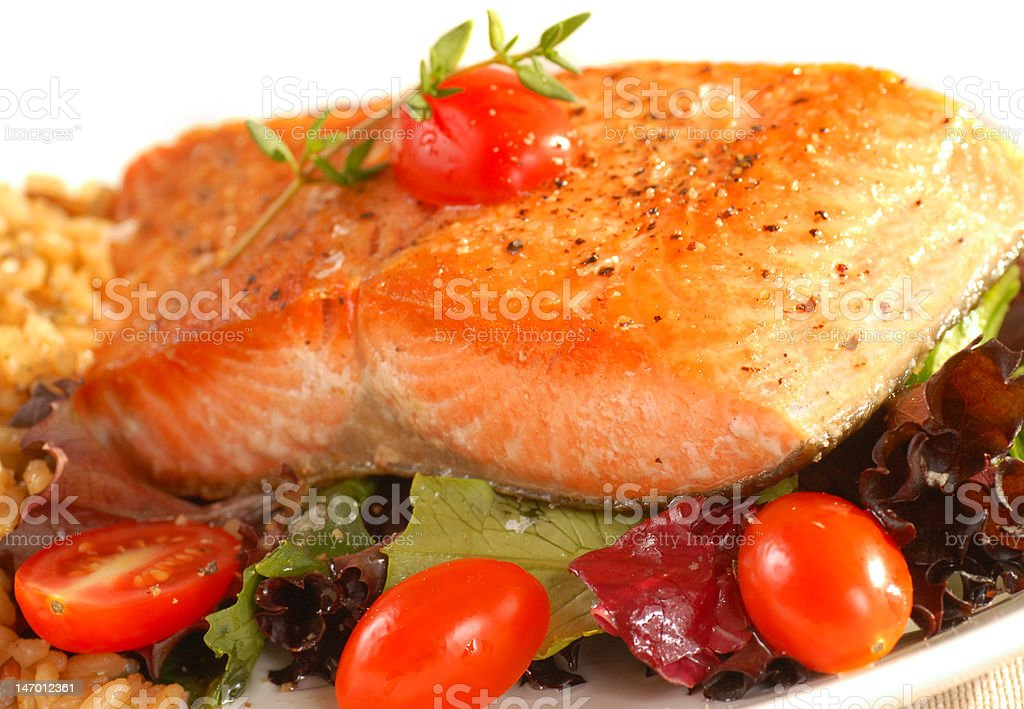 Sauted salmon on brown rice and greens royalty-free stock photo
