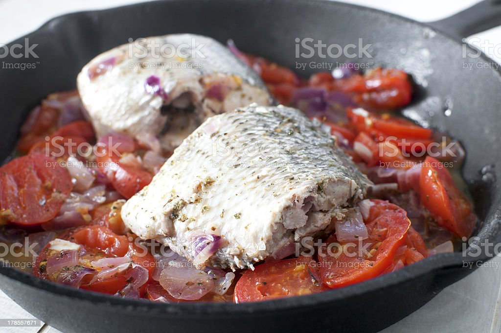 Sauteed bass pieces with tomatoes and onion royalty-free stock photo