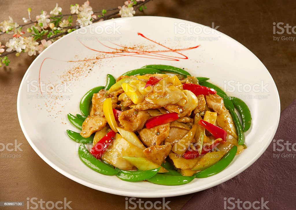 Sauteed green peas with chicken and chili on white plate stock photo