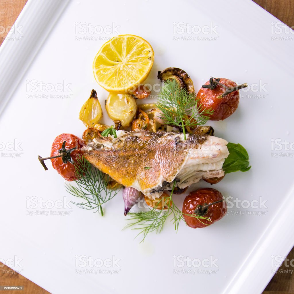 Sauteed Rockfish Fillet with Roasted Lemon and Vegetables stock photo