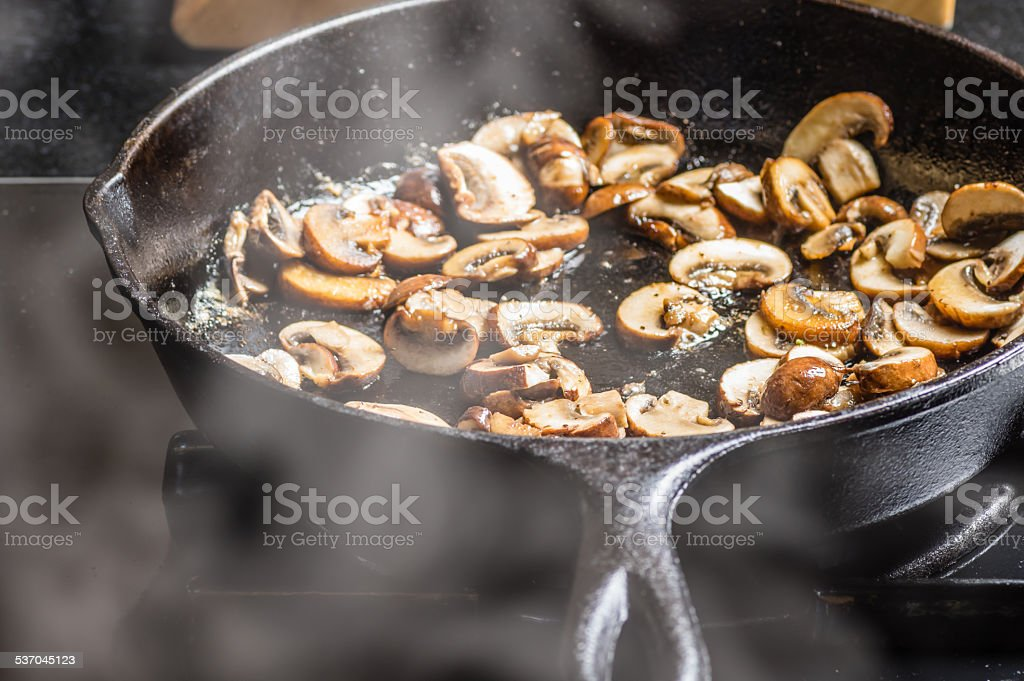 Sauteing sliced mushrooms in a skillet stock photo