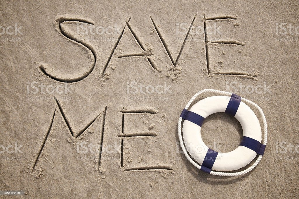 Save Me Message Handwritten in Sand with Lifesaver stock photo