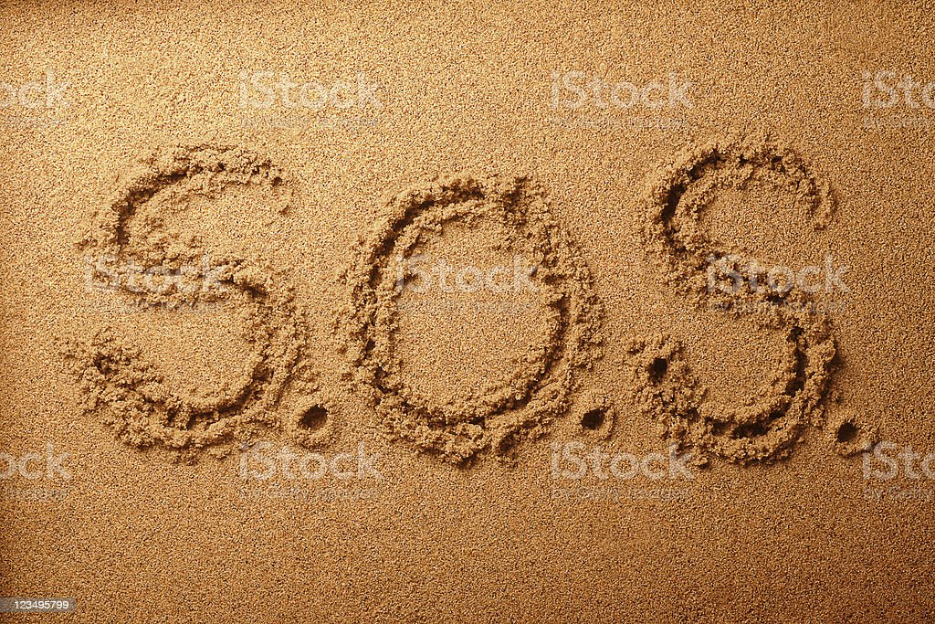 S.O.S 'Save Our Souls' written in the sand stock photo