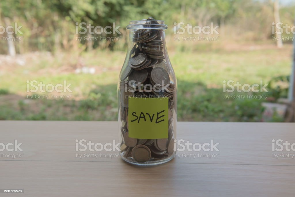 """""""Save"""" Writing in the paper, Coins in a glass jar stock photo"""
