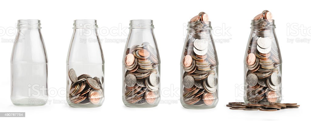 Saving coin in glass bottle stock photo