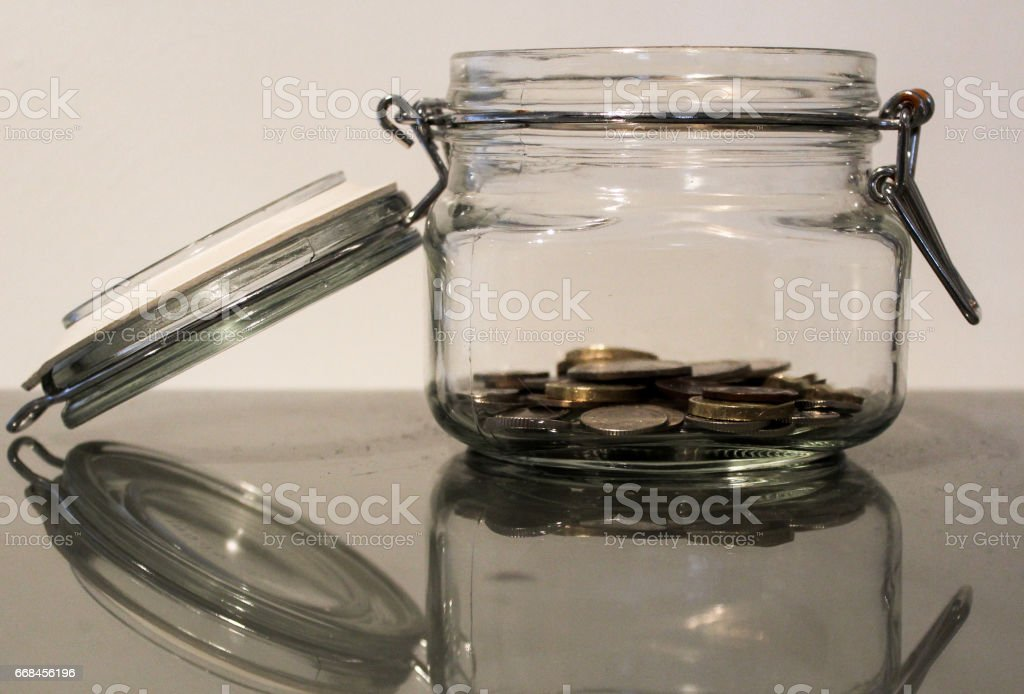 Saving money jar with small pile of coins stock photo