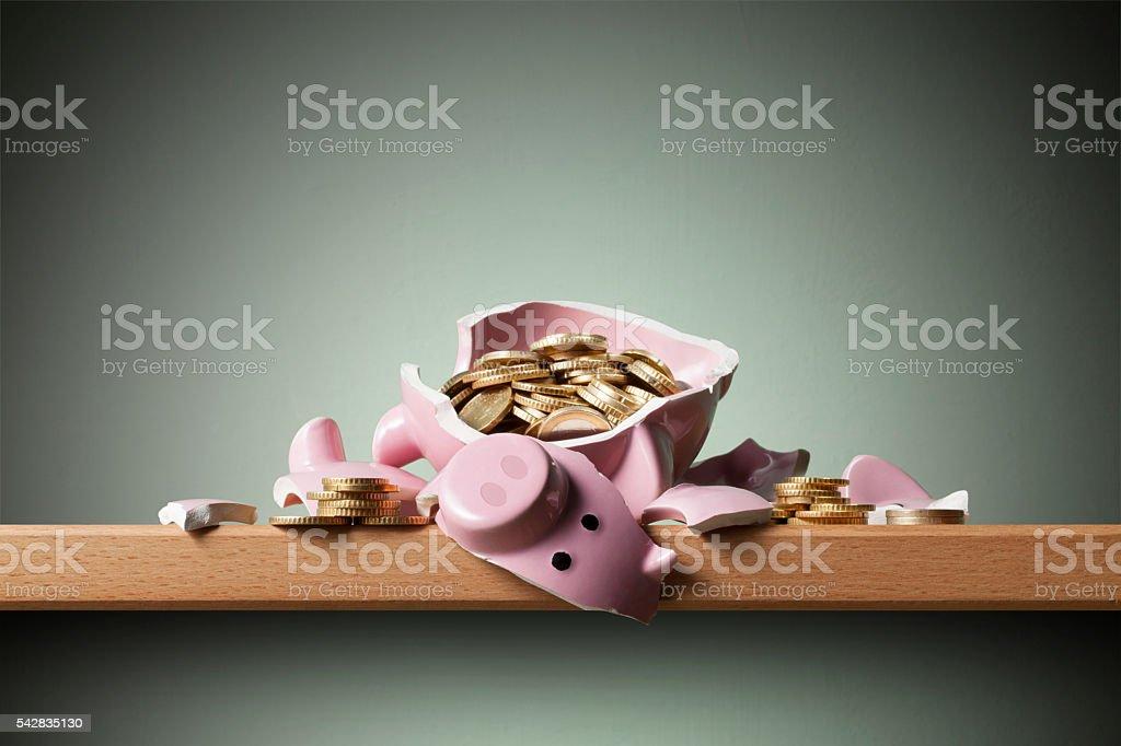 Savings. Broken piggy bank with coins. stock photo