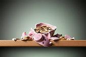 Savings. Broken piggy bank with coins.