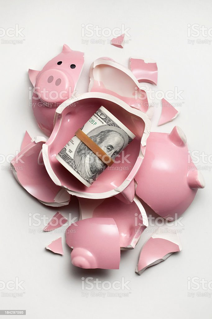 Savings. Broken piggy bank with dollars banknotes stock photo