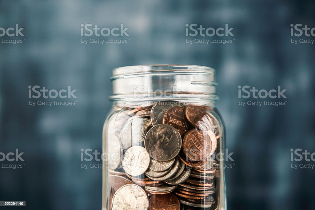 Savings jar filled with coins stock photo