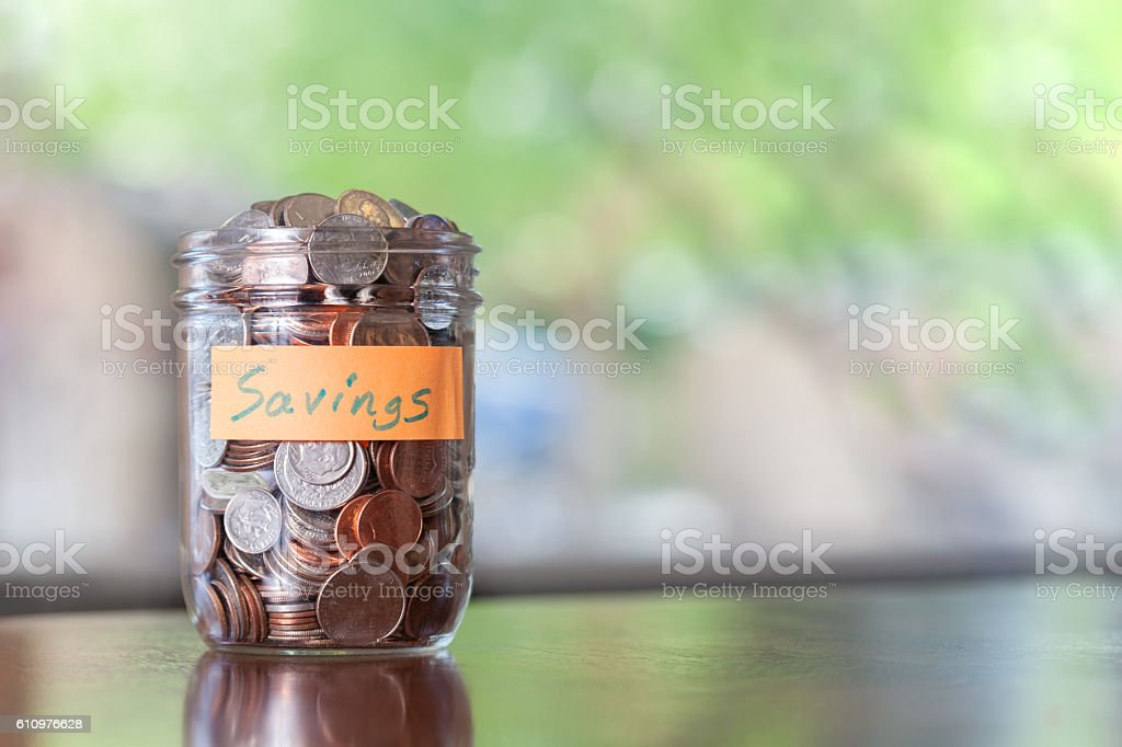 Savings jar full of coins stock photo