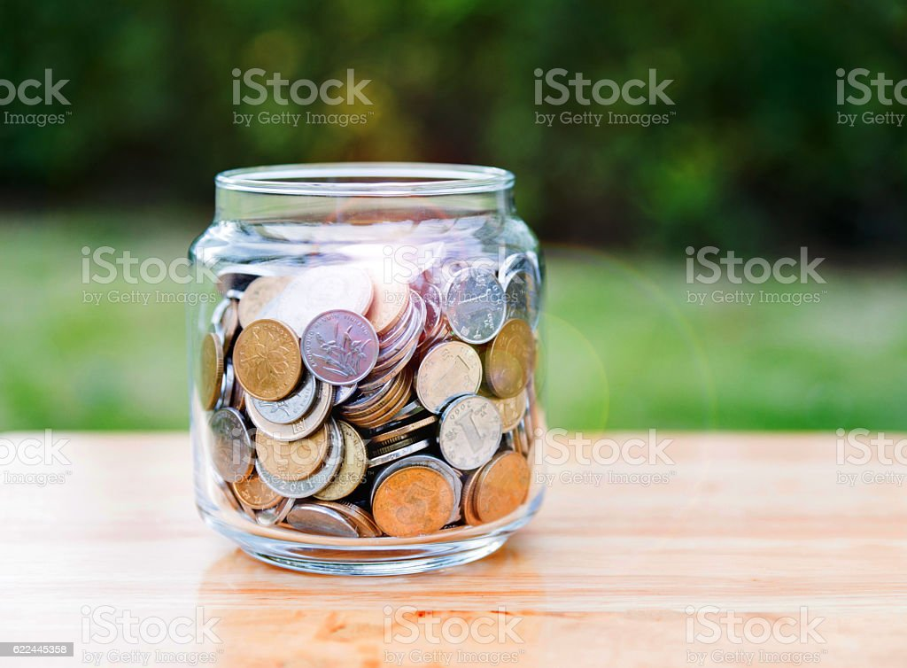 Savings jar with full of coins stock photo