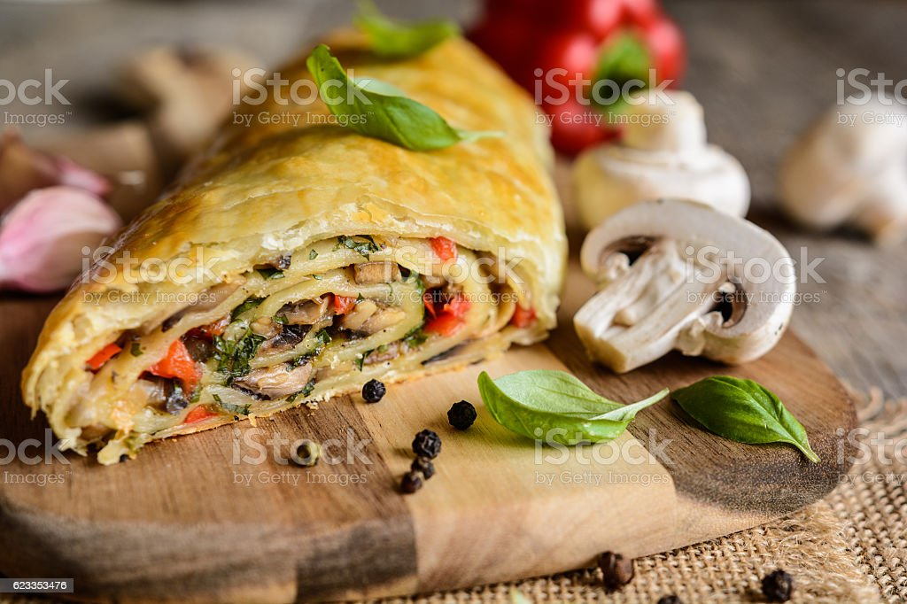 Savory strudel with mushrooms, red pepper, onion and garlic stock photo