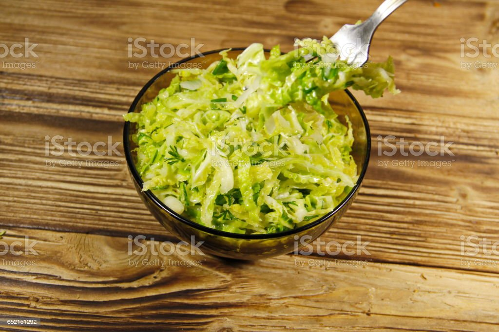 Savoy cabbage salad  in glass bowl on wooden table. Fork with salad stock photo