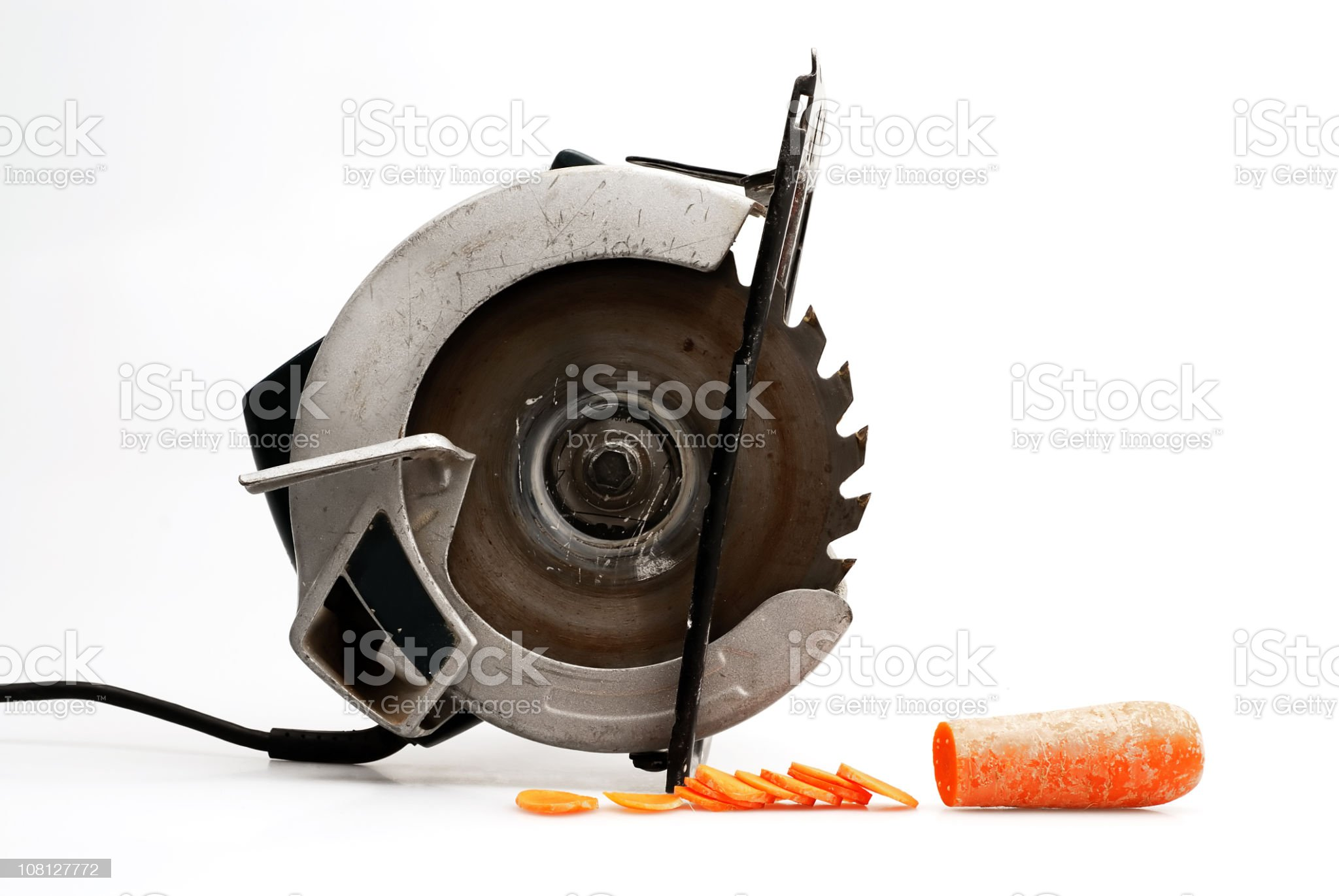 Saw Sitting Beside Cut Up Carrot Slice, On White Background royalty-free stock photo