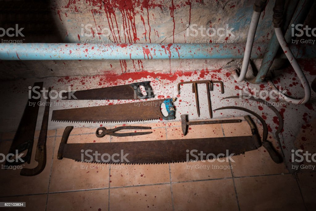 Saws, tongs and other devices on the bloody floor stock photo