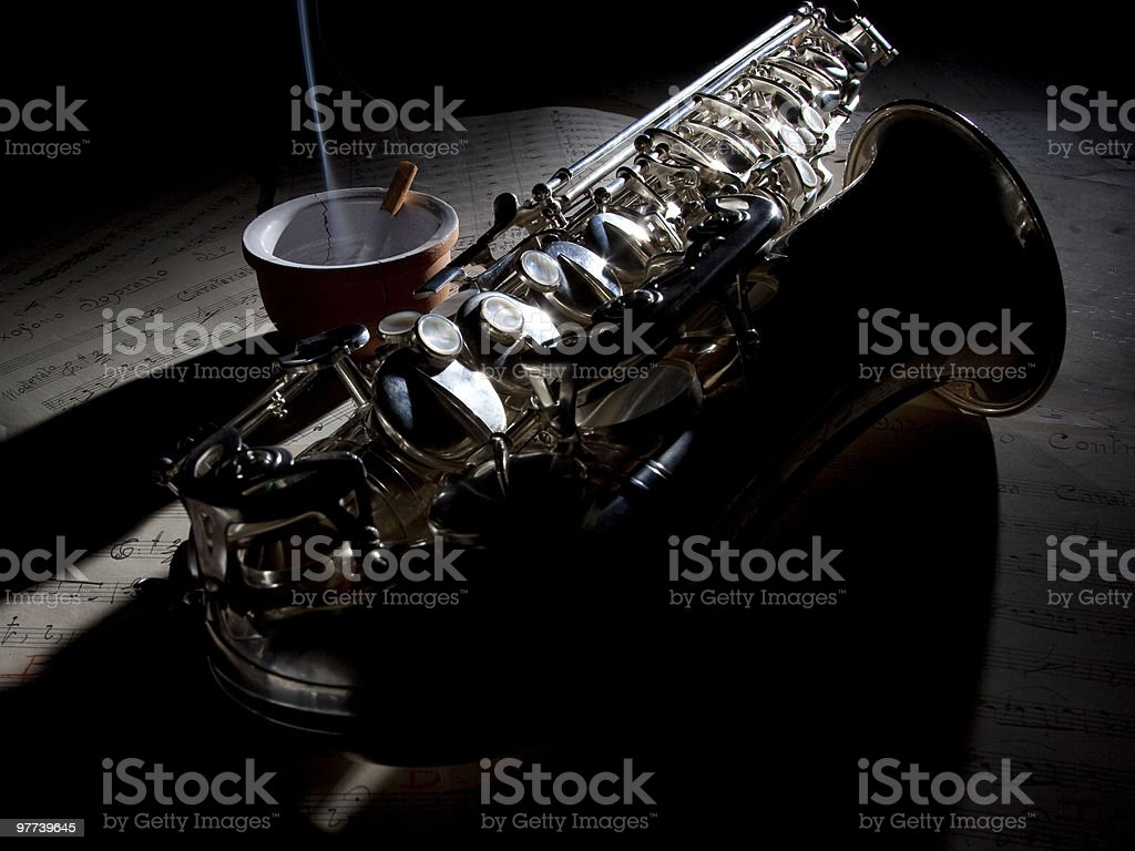 Saxophone cigarette and old sheet music royalty-free stock photo