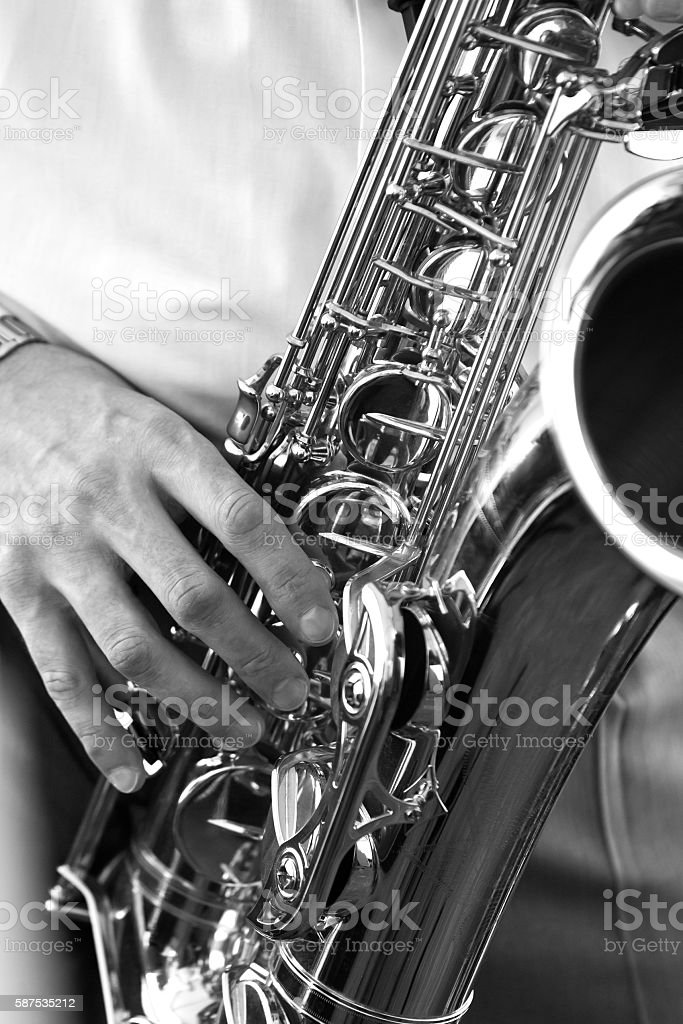 Saxophone in the hands of a musician of a closeup stock photo