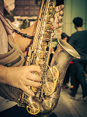 Saxophone in the hands on urban street. Music concept