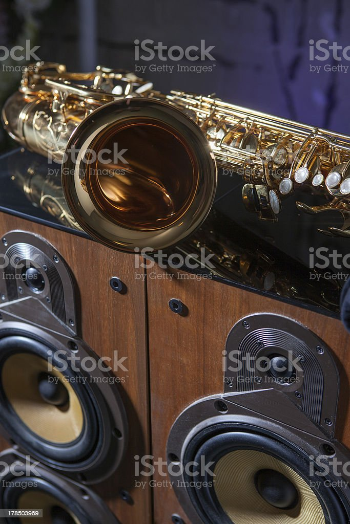 Saxophone resting on speakers in a recording studio royalty-free stock photo