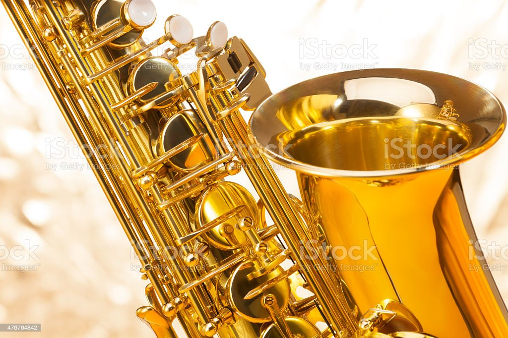 Saxophone with bell and keys on silver background stock photo