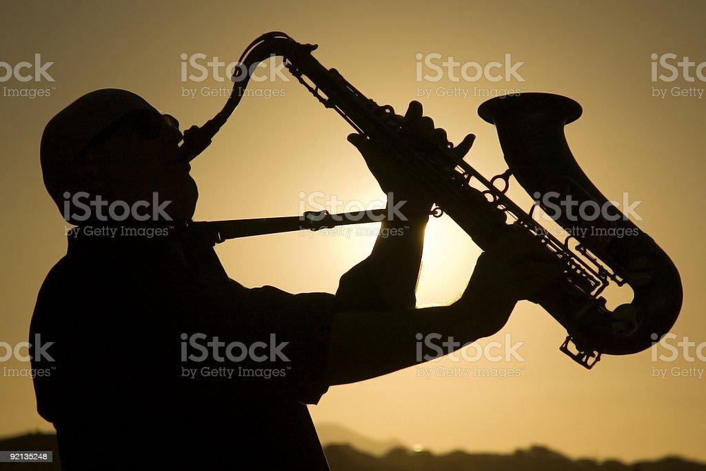 saxophonist at dusk 1 stock photo