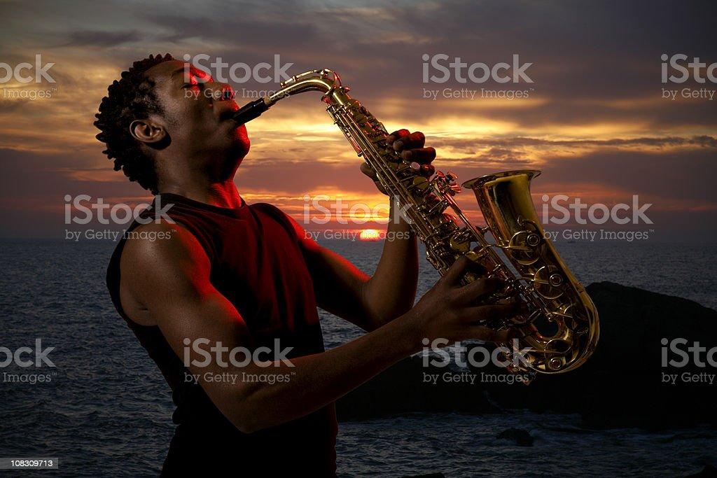 Saxophonist at sunset stock photo
