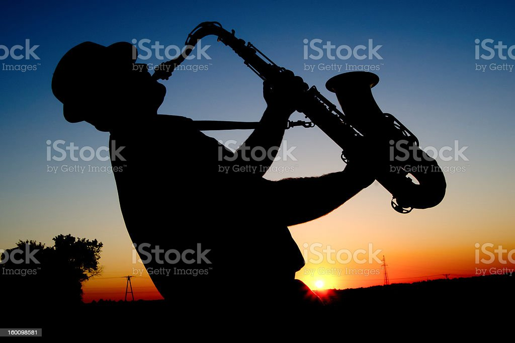 Saxophonist at sunset stock photo
