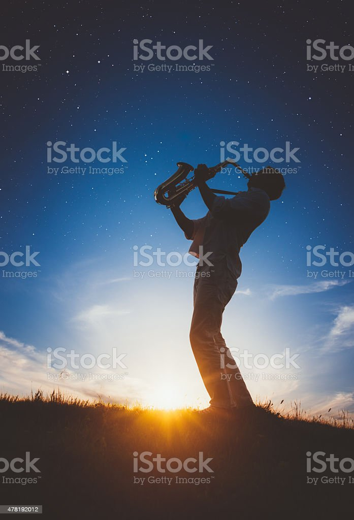 Saxophonist playing at sunset stock photo