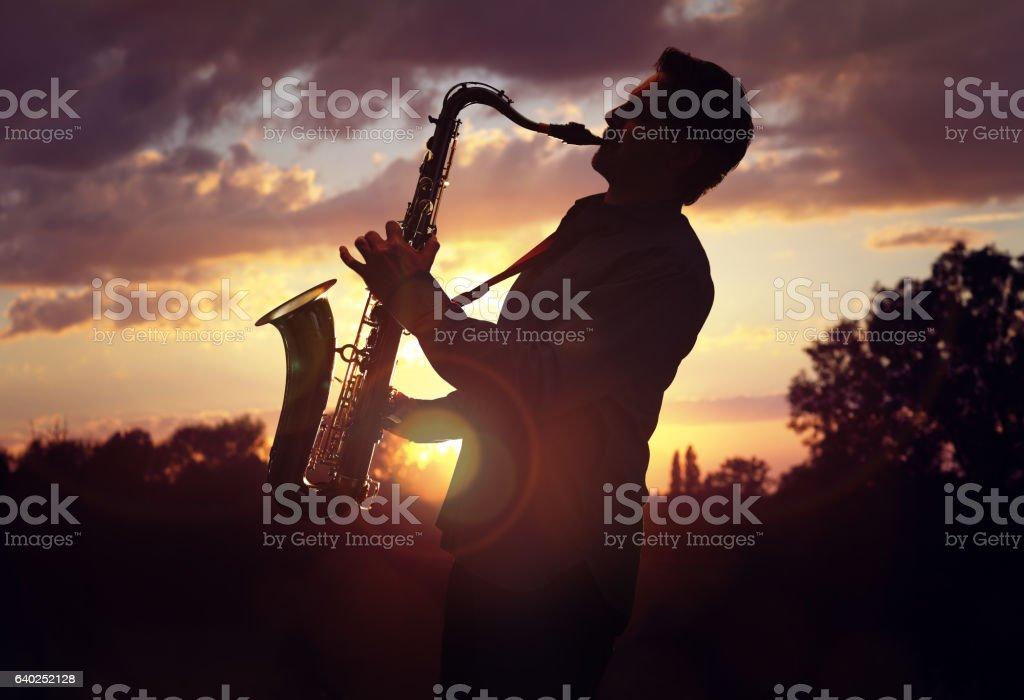 Saxophonist playing sax against sunset stock photo