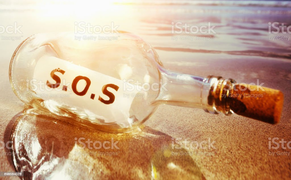 'SOS' says classic message in washed-up bottle stock photo