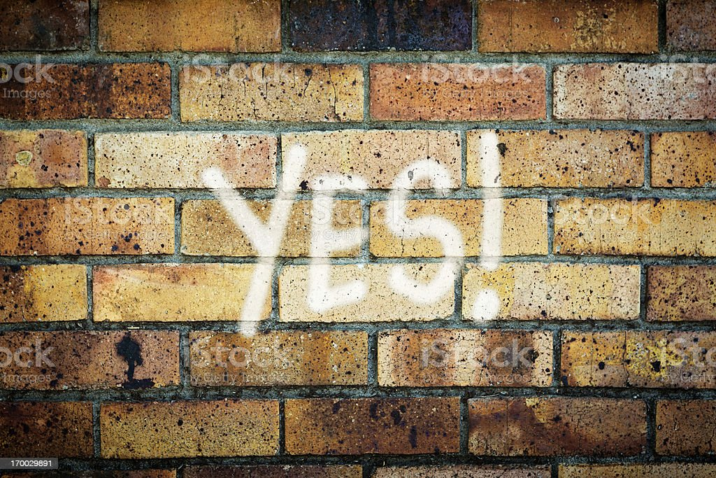 YES! says enthusiastic graffiti on grungy brick wall royalty-free stock photo