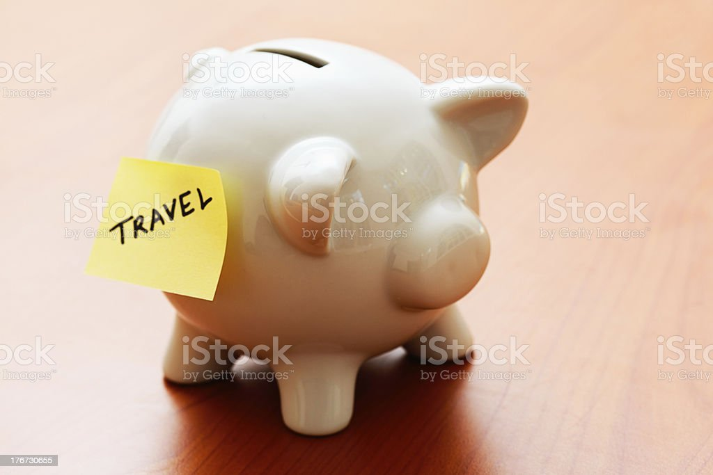 TRAVEL says label on piggybank: saving for a dream holiday! royalty-free stock photo