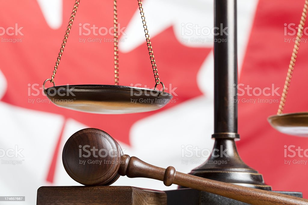Scale and gavel against Canadian flag royalty-free stock photo