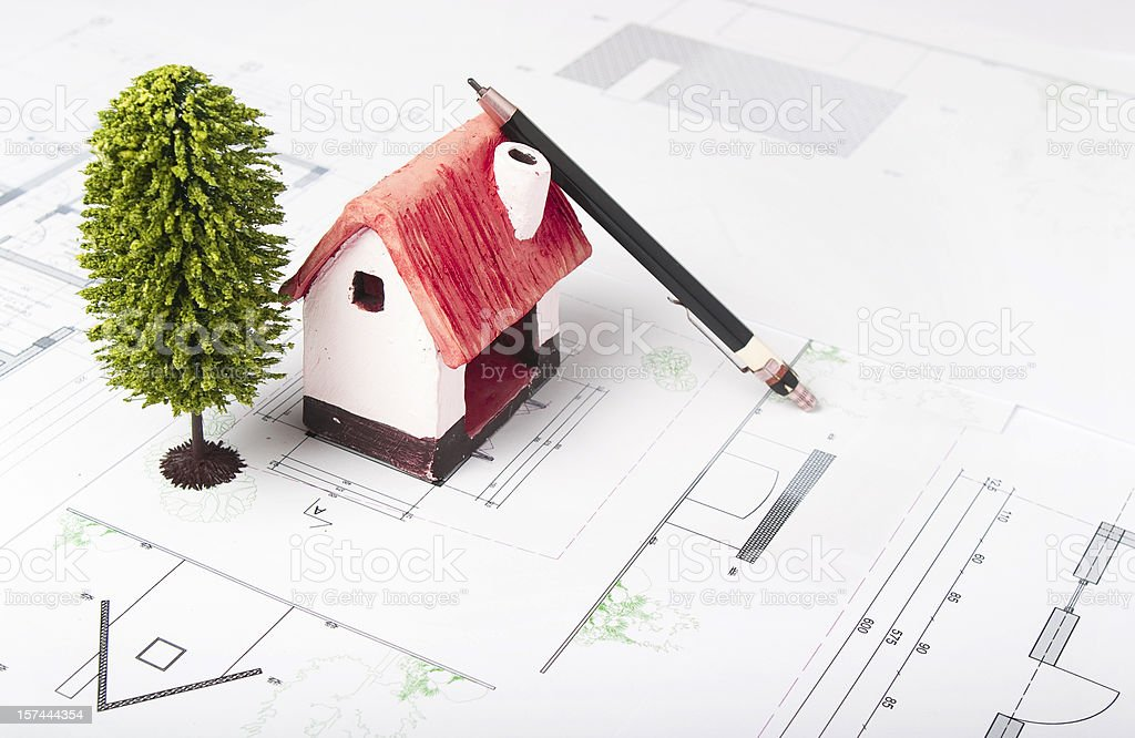Scale model of an ecological house and architecture blueprints royalty-free stock photo