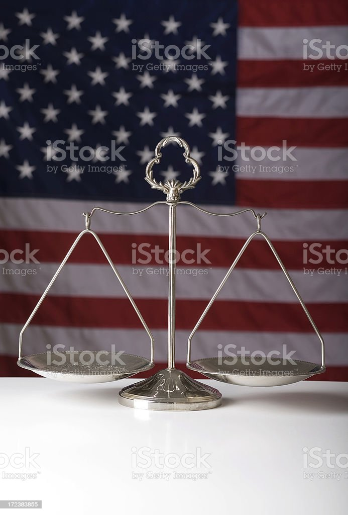 Scale of justice and American flag royalty-free stock photo