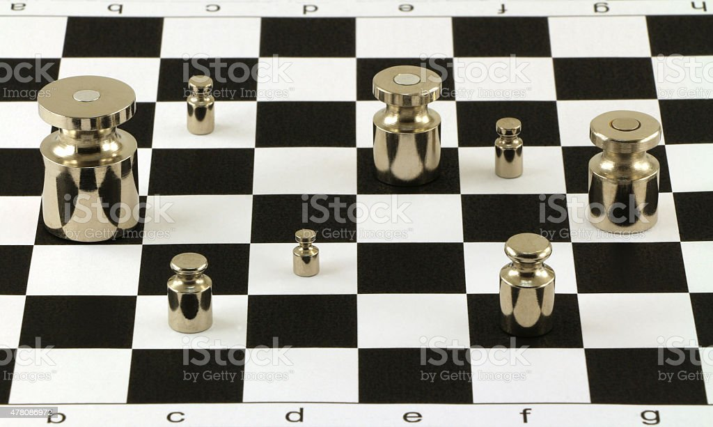 Scale steel shiny weights on chessboard surface stock photo