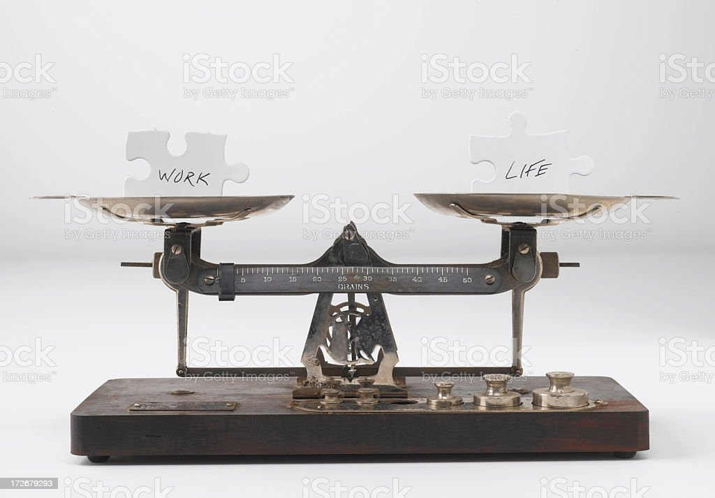 A scale with puzzle pieces balancing that read work and life royalty-free stock photo