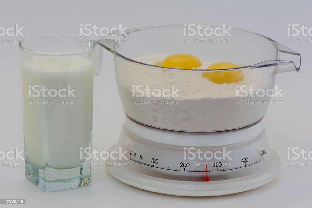 scales with flour and a yolk and milk stock photo