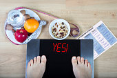 Scales with sign'yes' surrounded by healthy lifestyle accessories.