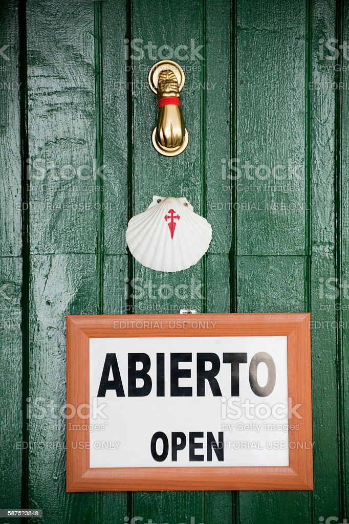 Scallop symbol, open sign and brass knocker on green door. stock photo