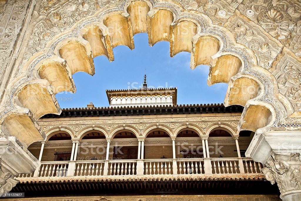 Scalloped archway frames balcony of Royal Alcazars in Spain stock photo