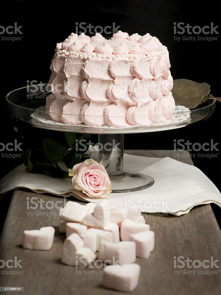 Scalloped pale pink cake on glass stand next to rose. royalty-free stock photo