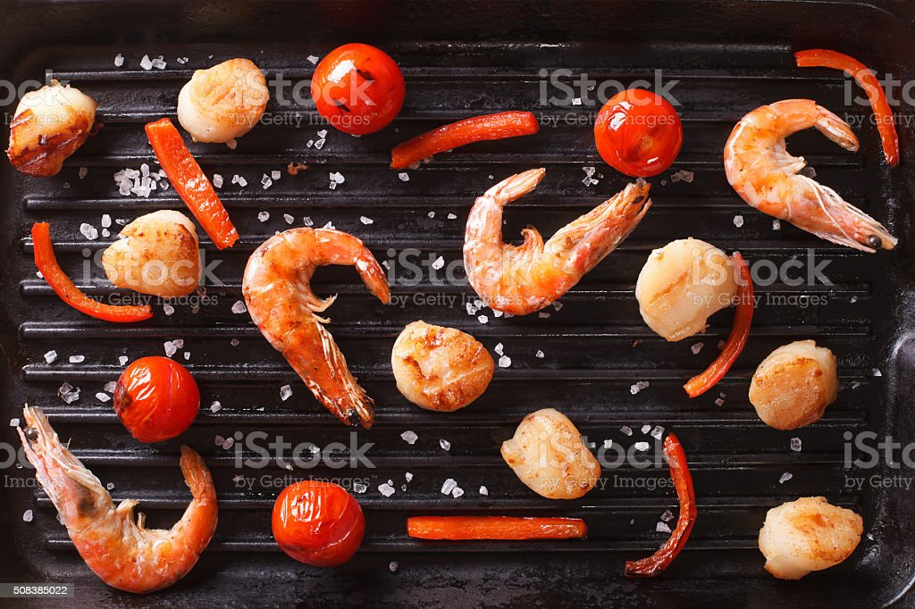 Scallops and shrimp on the grill closeup. horizontal top view stock photo